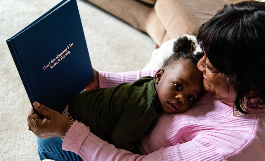 Great-grandmother and great-granddaughter sit with photo book