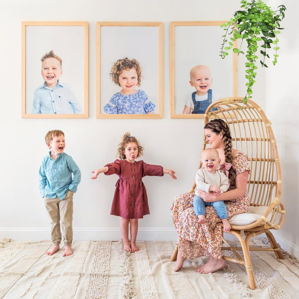 kids with their photos on wall
